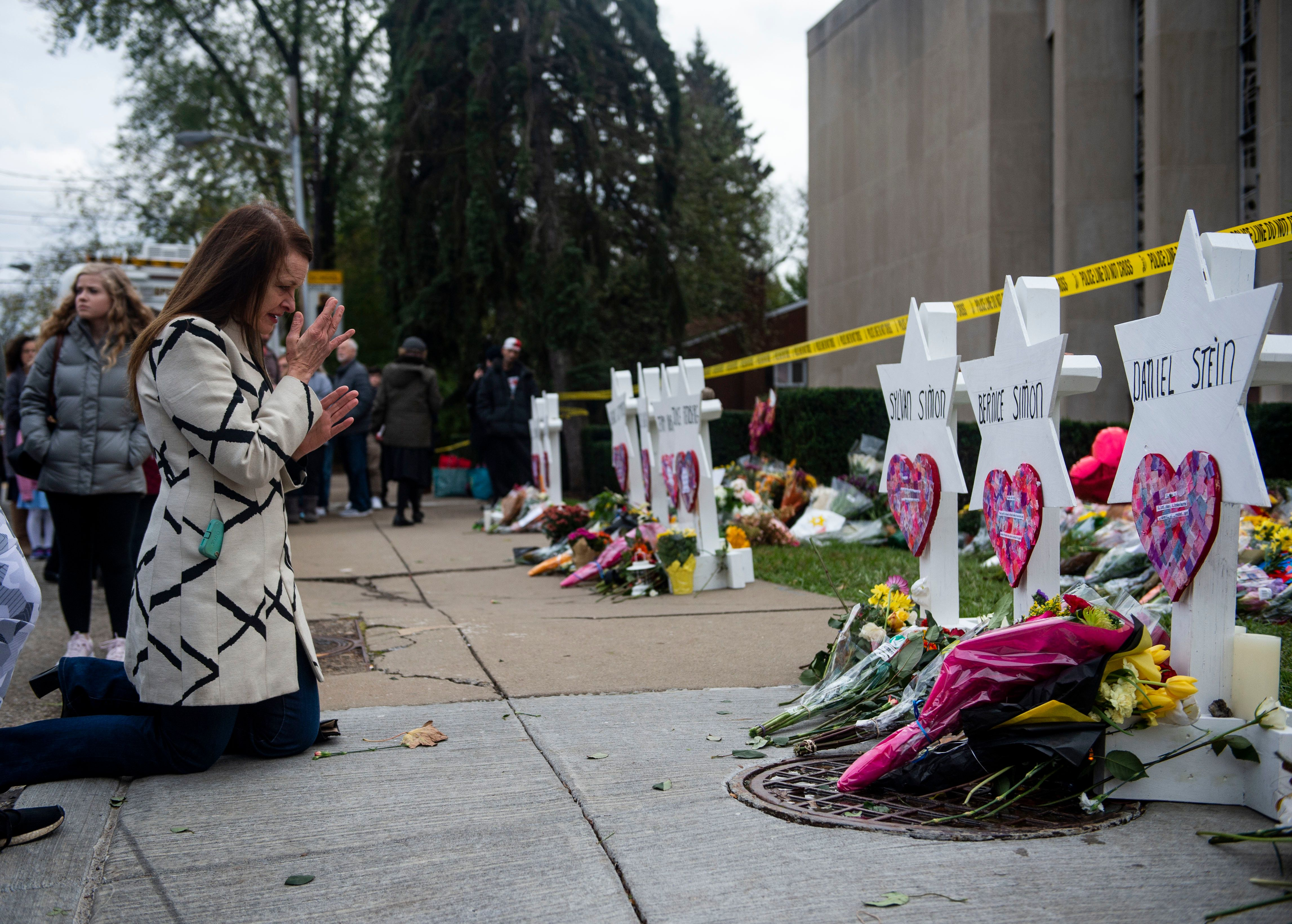 A woman prays outside the Tree of Life synagogue in Pittsburgh, where a white supremacist killed 11 people.