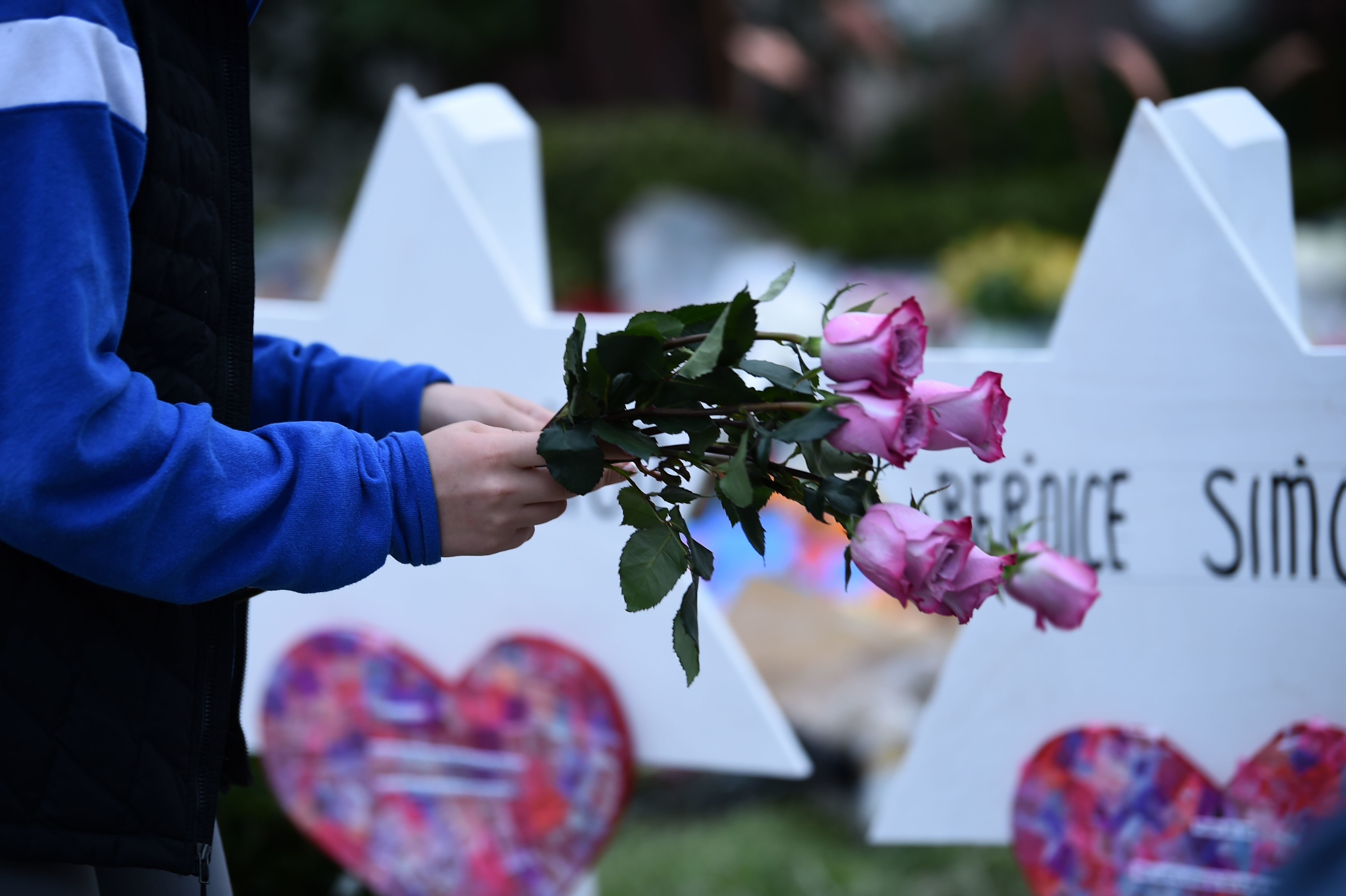 People pay their respects at a memorial outside the Tree of Life synagogue after a shooting there left 11 people dead in the Squirrel Hill neighborhood of Pittsburgh, Pennsylvania on October 29, 2018. - Mourners held an emotional vigil Sunday for victims of a fatal shooting at a Pittsburgh synagogue, an assault that saw a gunman who said he 'wanted all Jews to die' open fire on a mostly elderly group. Americans had earlier learned the identities of the 11 people killed in the brutal assault at the Tree of Life synagogue, including 97-year-old Rose Mallinger and couple Sylvan and Bernice Simon, both in their 80s.Nine of the victims were 65 or older. (Photo by Brendan SMIALOWSKI / AFP)        (Photo credit should read BRENDAN SMIALOWSKI/AFP/Getty Images)