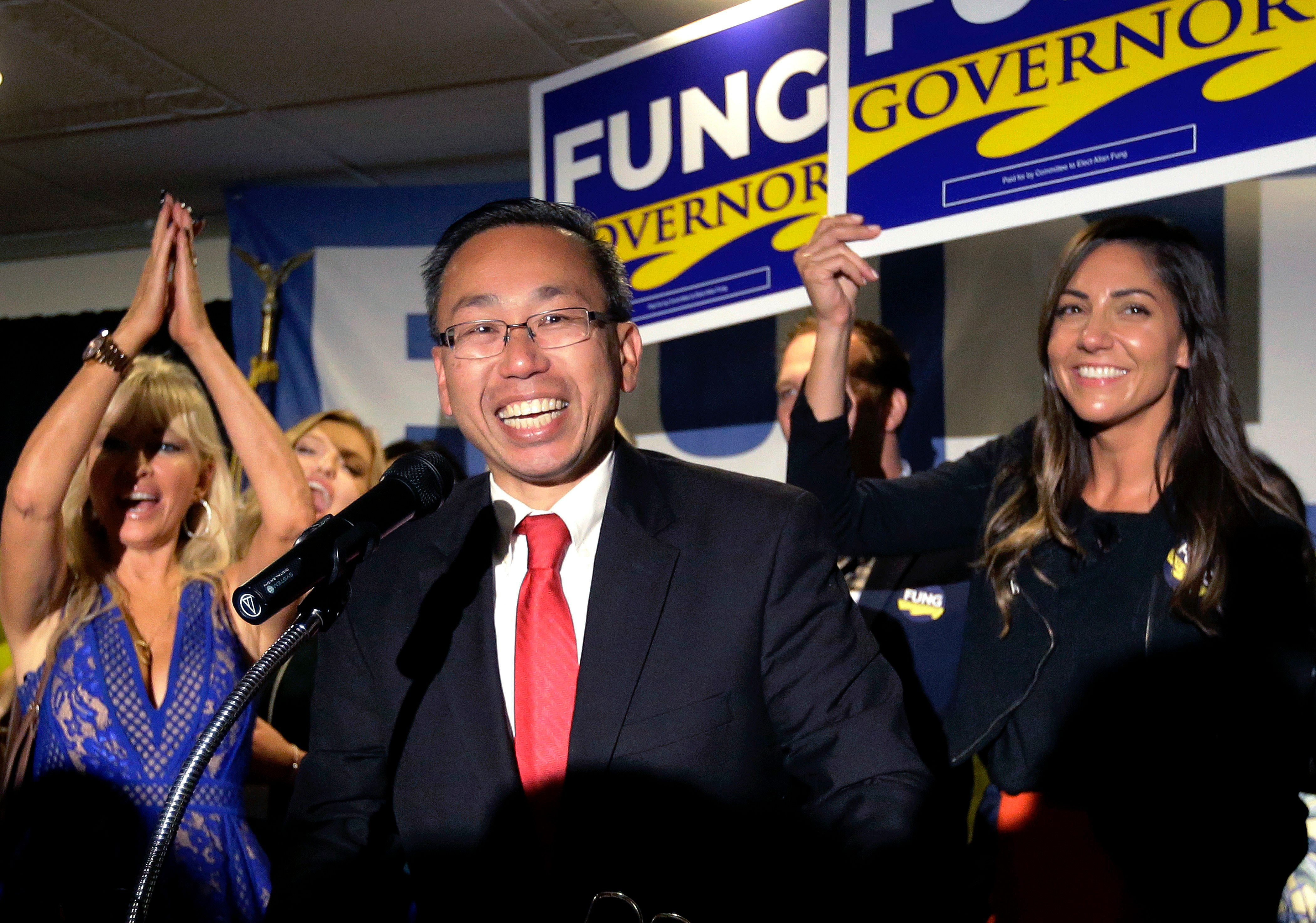 Cranston, R.I., Mayor Allan Fung, center, celebrates victory over R.I. House Minority Leader Patricia Morgan in the Republican gubernatorial primary, Wednesday, Sept. 12, 2018, in Cranston, R.I. (AP Photo/Steven Senne)