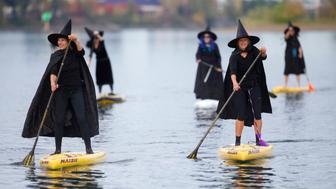 Hundreds of witches, along with a handful of warlocks and wizards, tossed their broomsticks, grabbed paddles and traveled six miles along the Willamette River Saturday, Oct. 27, 2018. The event, called Standup Paddleboard Witch Paddle, dodged days of rain catching a short window of sunshine for the entire three-hour event. The costumed coven cruised for six miles along the Willamette River, which divides the city of Portland.  (Mark Graves/The Oregonian via AP)