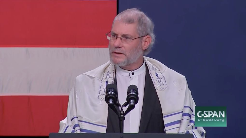 """Loren Jacobs, a Christian """"rabbi,"""" says a prayer at a Republican rally headlined by Vice President Mike Pence in Oakland, Michigan, on Monday."""