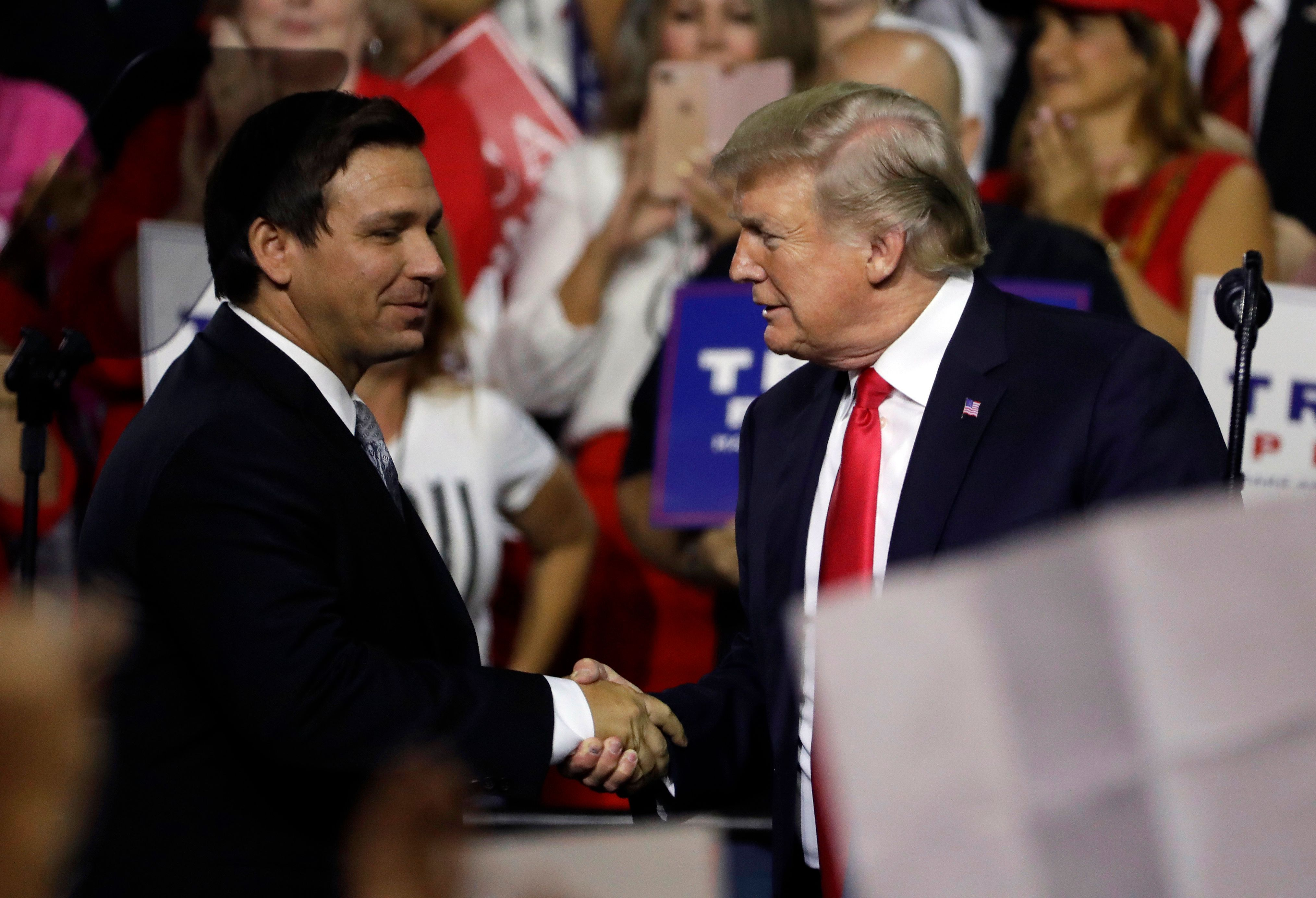 President Donald Trump, right, shakes hands with Florida Republican gubernatorial candidate Ron DeSantis during a rally Tuesday, July 31, 2018, in Tampa, Fla. (AP Photo/Chris O'Meara)