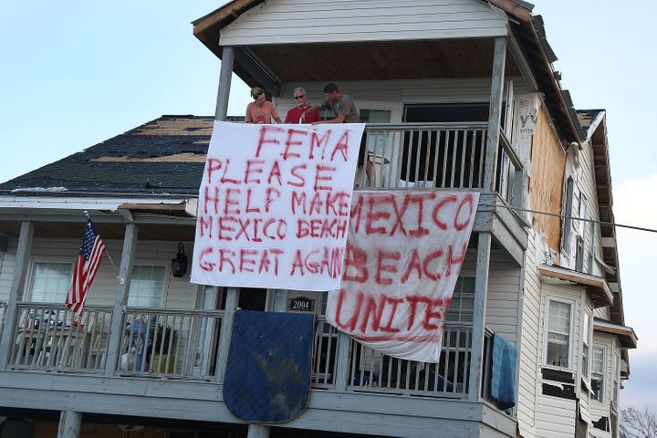 Residents hang a sign out that reads, 'FEMA Please Help Make Mexico Beach Great Again' outside their home that was damaged by