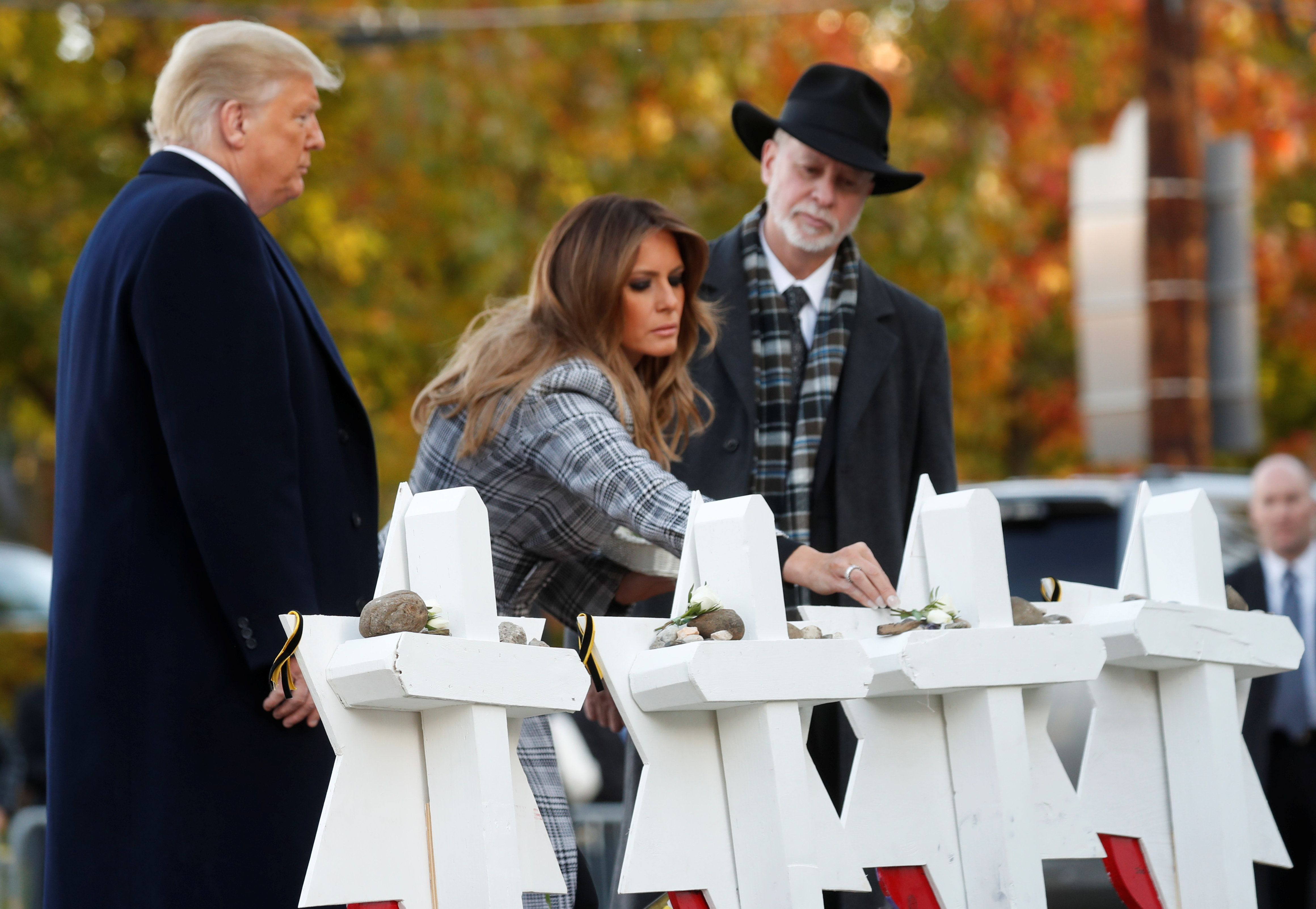 U.S. President Donald Trump and first lady Melania Trump place stones on a memorial to shooting victims as they stand with Tree of Life Synagogue Rabbi Jeffrey Myers outside the synagogue where a gunman killed eleven people and wounded six during a mass shooting in Pittsburgh, Pennsylvania, U.S., October 30, 2018. REUTERS/Kevin Lamarque