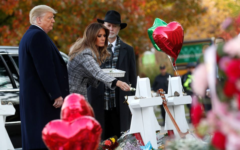 President Donald Trump watches as first lady Melania Trump places a flower on a memorial to shooting...