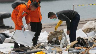 An investigator, right, examines parts of Lion Air Flight 610 retrieved from the waters off Tanjung Priok in Jakarta, Indonesia, Wednesday, Oct. 31, 2018. A massive search effort identified the possible seabed location of the crashed Lion Air jet, Indonesia's military chief said Wednesday, as experts carried out the grim task of identifying dozens of body parts recovered from a 15-nautical-mile-wide search area. (AP Photo/Tatan Syuflana)