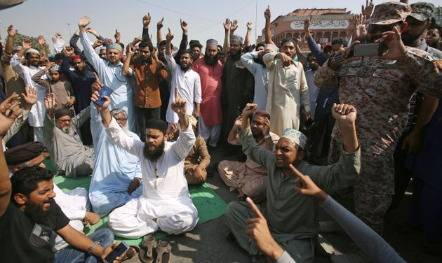 Supporters of a Pakistani religious group in Karachi chant slogans while blocking a main road at a protest...