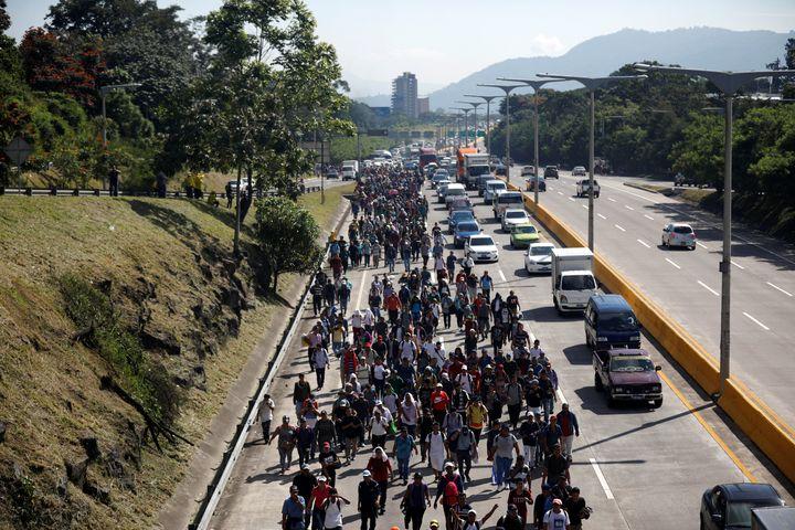 People walk in a caravan of migrants departing from El Salvador en route to the United States, in San Salvador, El Salvador,