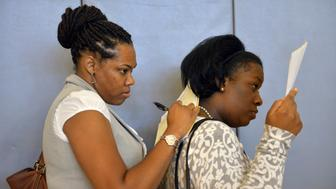 FORT WASHINGTON, MD  - SEPTEMBER 17:   J.C. (only wants to use her initials), L, of Temple Hills, MD, uses the back of Lawanda Prescott, R, of Capitol Heights, MD, to fill out a job application as thousands of applicants attend a job fair hosted by Tanger Outlets for its November opening on Tuesday, September 17, 2013, in Fort Washington, MD.  The center at National Harbor will bring 900 jobs to Prince George's County.  Event organizers said the job fair attracted roughly 1,000 applicants per hour and they are expecting to receive about 6-7,000 applicants by day's end.  (Photo by Jahi Chikwendiu/The Washington Post via Getty Images)