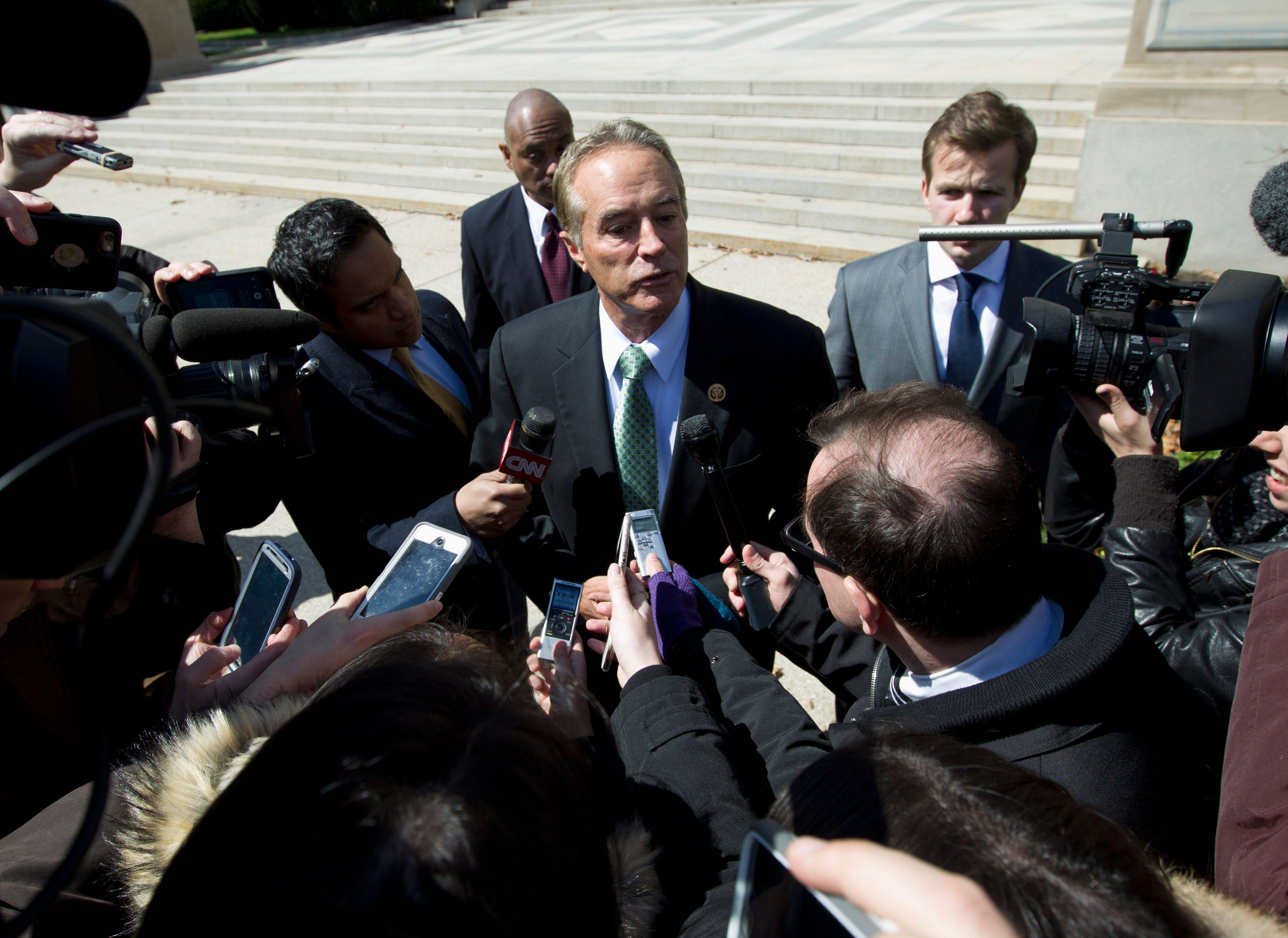 FILE - In this March 21, 2016, file photo, Rep. Chris Collins, R-N.Y., speaks with reporters as he leaves a closed-door meeting with Republican presidential candidate Donald Trump in Washington.  Winning re-election while indicted is a rare feat in U.S. history. But two congressmen are attempting to do just that in this midterm election: Rep. Duncan Hunter of California and Rep. Chris Collins of New York. The first Republican lawmakers to endorse President Donald Trump are now running low-profile campaigns, avoiding the media and meeting with voters at Republican friendly events.  ( AP Photo/Jose Luis Magana, File)