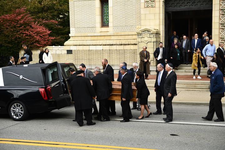 Mourners gather as a casket is carried outside the Rodef Shalom Congregation, where the funeral for shooting victims Cecil Ro