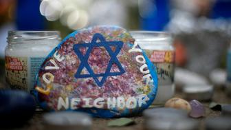This is a painted rock found Wednesday, Oct. 31, 2018, part of a makeshift memorial outside the Tree of Life Synagogue in the Squirrel Hill neighborhood of Pittsburgh, to the 11 people killed during worship services Saturday Oct. 27, 2018. (AP Photo/Gene J. Puskar)