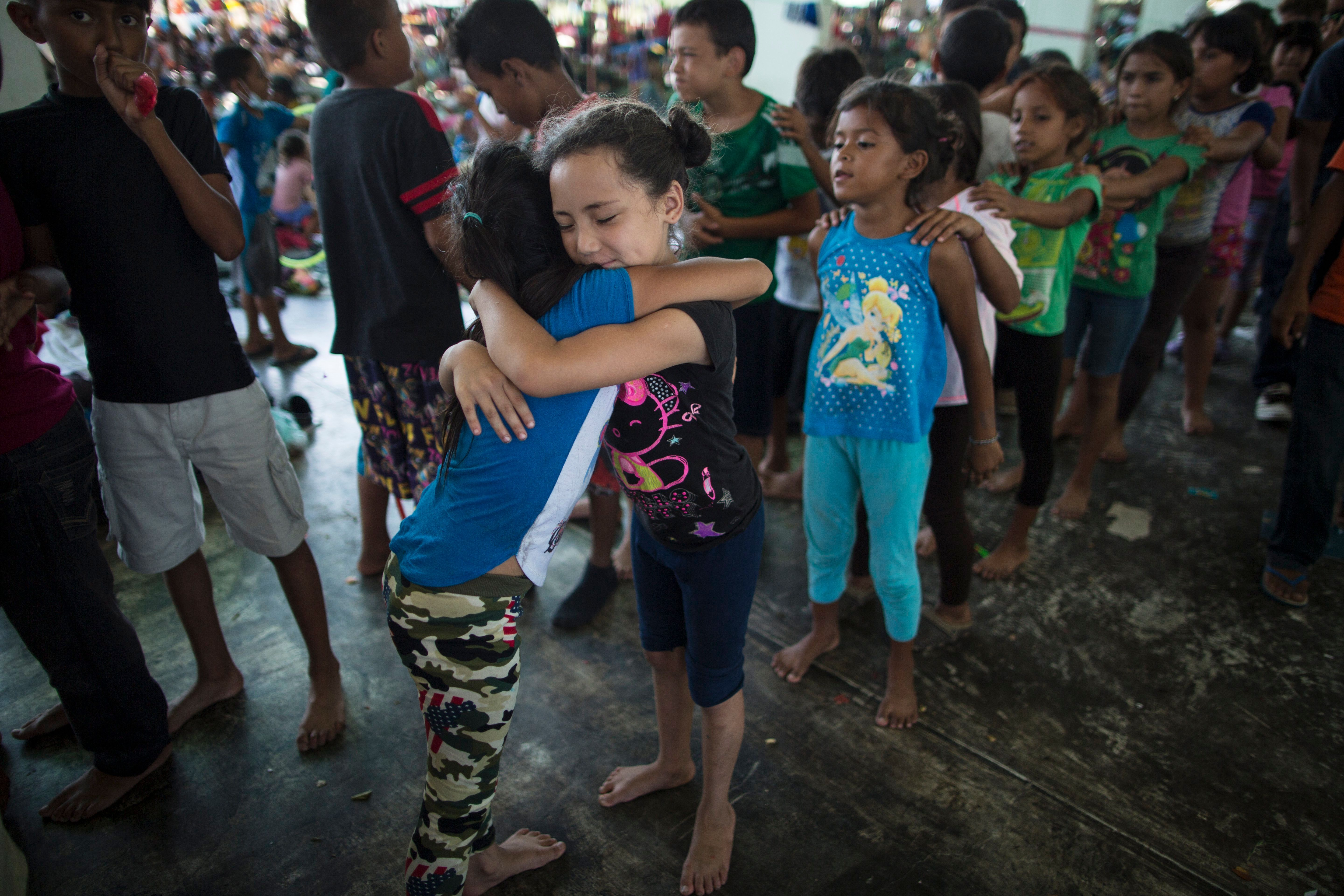 Honduran girls hug while waiting in line for a chance to play on the playground at a camp set up by a caravan of thousands of