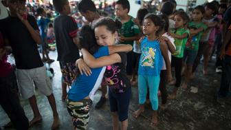 Honduran girls hug while waiting in line for a chance to play on the playground at a camp set up by a caravan of thousands of Central American migrants in Juchitan, Mexico, Wednesday, Oct. 31, 2018. Representatives of the group sought Wednesday to negotiate use of dozens of buses to carry the migrants hundreds of miles ahead, as the caravan took at least a day off from the grind of walking and hitching rides in packed trucks from small town to small town. (AP Photo/Rodrigo Abd)