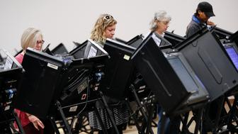 Voters use electronic polling machines as they cast their votes early at the Franklin County Board of Elections, Wednesday, Oct. 31, 2018, in Columbus, Ohio. (AP Photo/John Minchillo)
