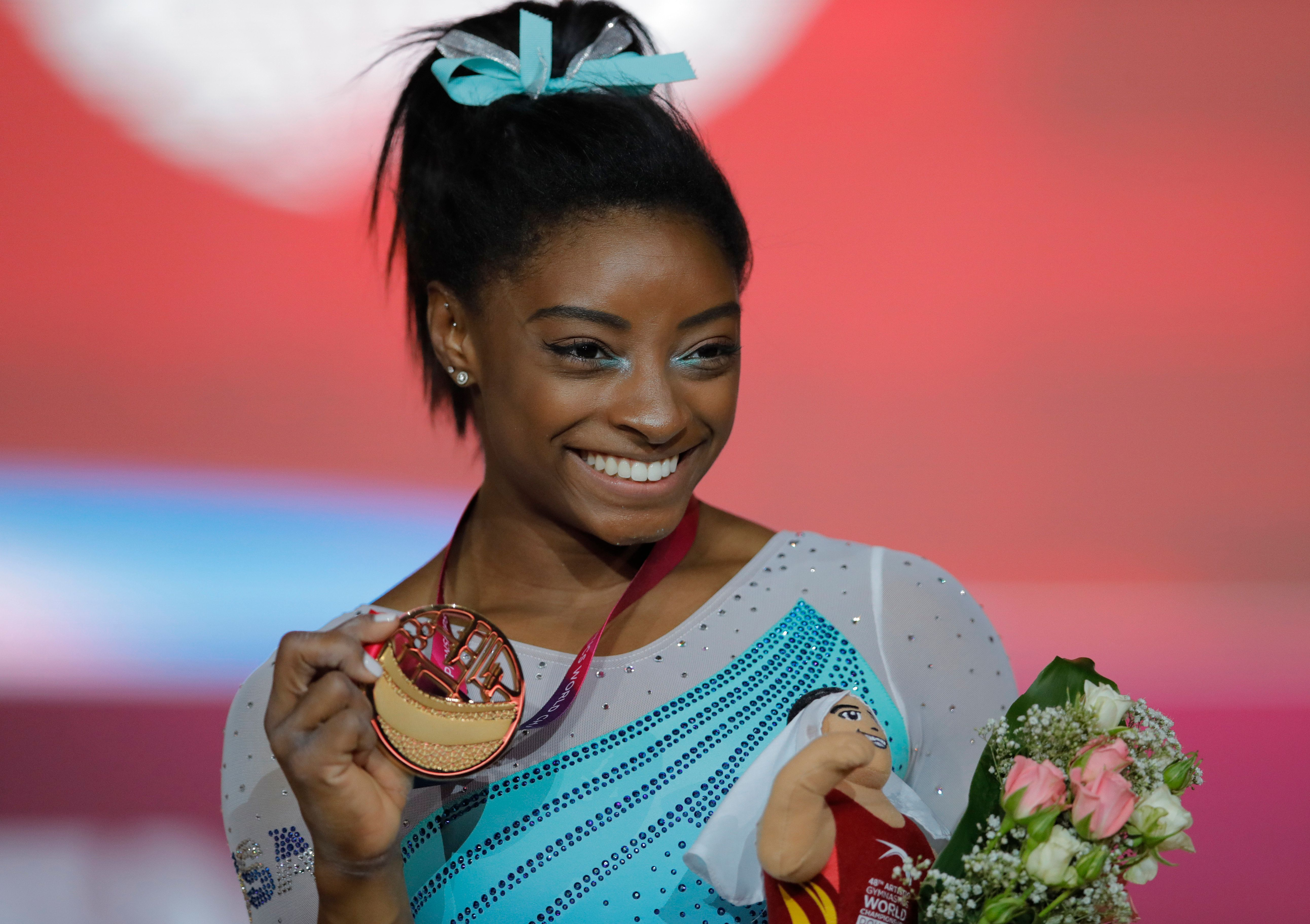 Gold medallist and four-times All-Around world champion Simone Biles of the U.S., poses on the podium after the Women's All-Around Final of the Gymnastics World Chamionships at the Aspire Dome in Doha, Qatar, Thursday, Nov. 1, 2018. (AP Photo/Vadim Ghirda)