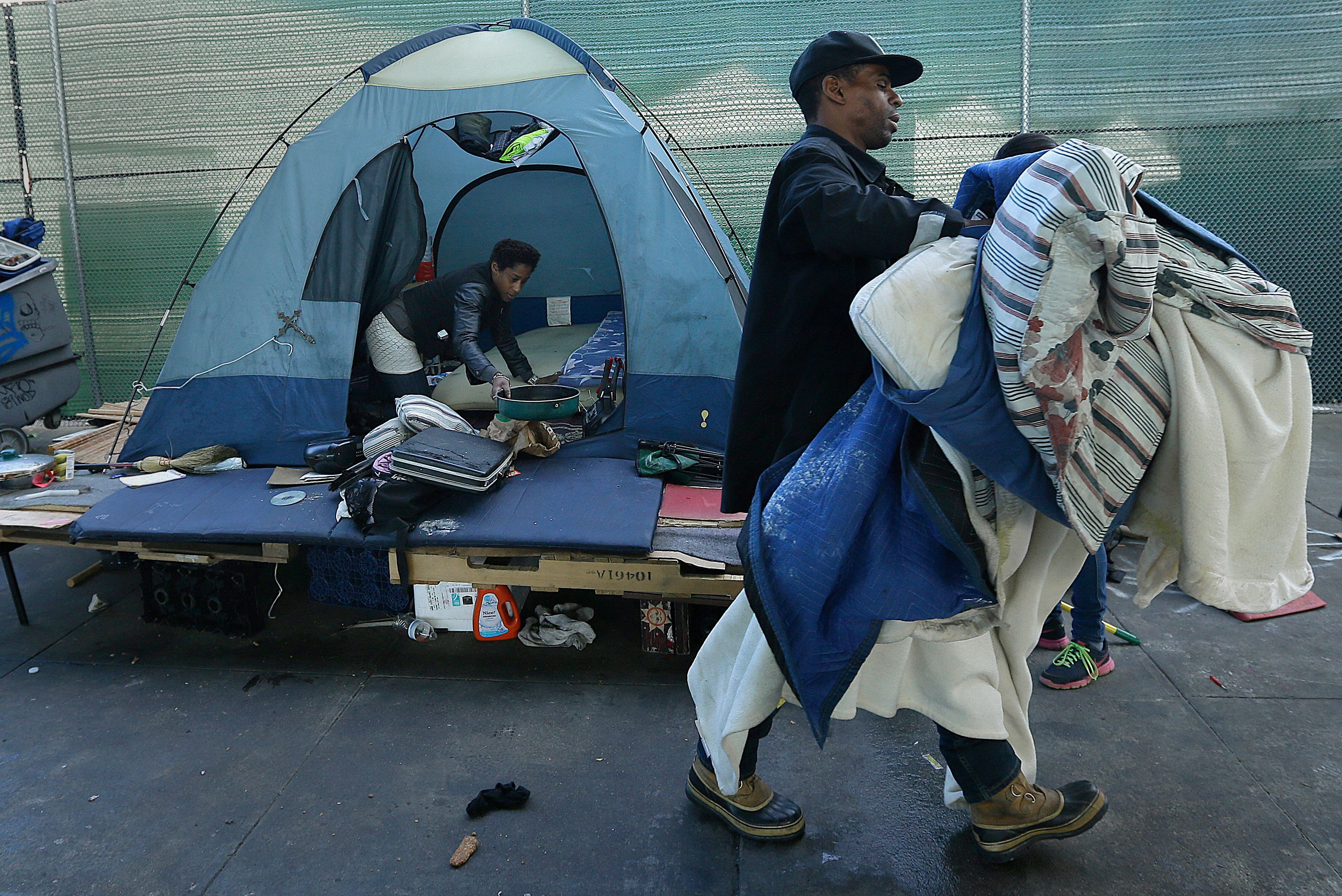 A homeless couple gather their belongings in San Francisco, Tuesday, March 1, 2016. Crews in San Francisco on Tuesday began sweeping out a homeless camp under the city's Central Freeway that was declared a health hazard and for months has been a source of irritation for neighbors and nearby businesses. (AP Photo/Ben Margot)