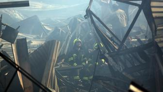 Firefighters rest at the site of a fire at an electronic appliances market in Kabul, Afghanistan, Friday, Nov. 2, 2018. Residents of the Afghan capital are grappling with the aftermath of a massive blaze that destroyed hundreds of stores at a market in Kabul.(AP Photo/Massoud Hossaini)