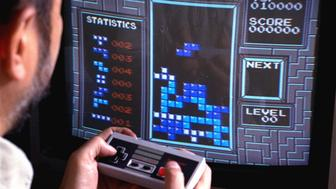 """FILE - In this June 1990 file photo, Tetris, an addictive brain-teasing video game, is shown as played on the Nintendo Entertainment System in New York. From the simple """"pings"""" of the ground-breaking """"Pong"""" in 1972, video game music has come of age, with its own culture, sub-cultures and fans. This weekend, June 17-18, 2017, audiences will pack the Philharmonie de Paris' concert hall to soak in the sounds of orchestras performing video game music and wallow in the nostalgia of hours spent with a Game Boy, Sonic the Hedgehog and the evergreen Mario. (AP Photo/Richard Drew, File)"""