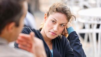 A woman listening to a man (defocussed) talking during a discussion at an outdoor cafe.