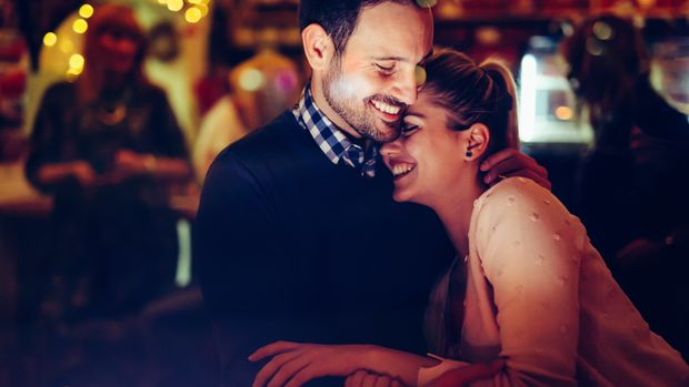 Romantic young couple dating in pub at night
