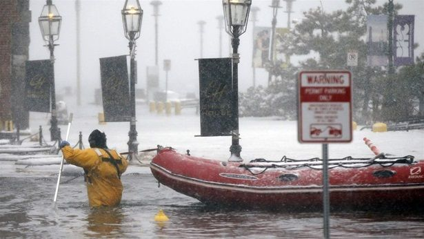A firefighter wades through Boston floodwater earlier this year. Under a new plan, the city would allow the rising water to c
