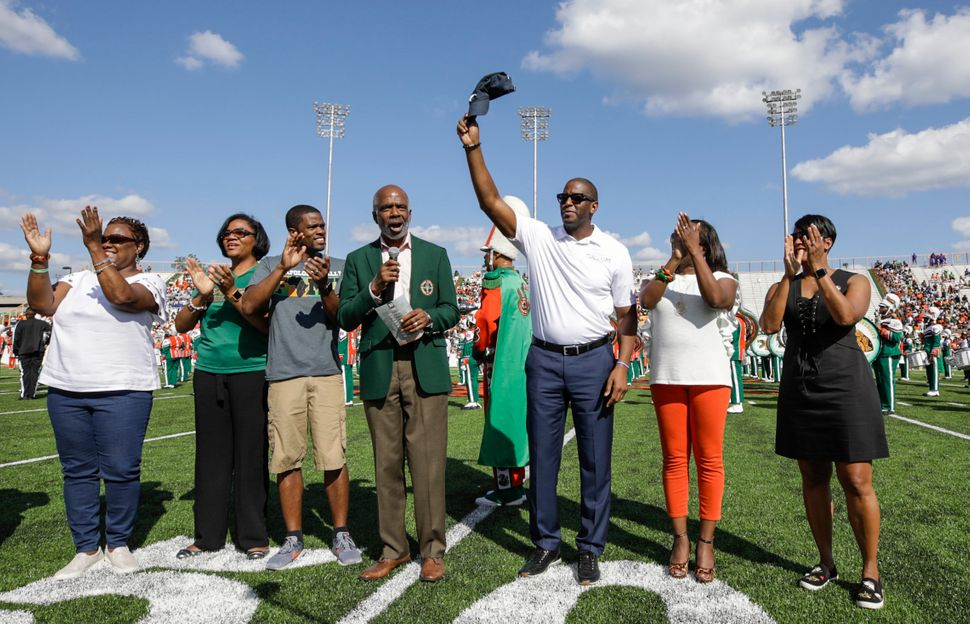 The Gillums stand with other FAMU alumni during the homecoming football game coin