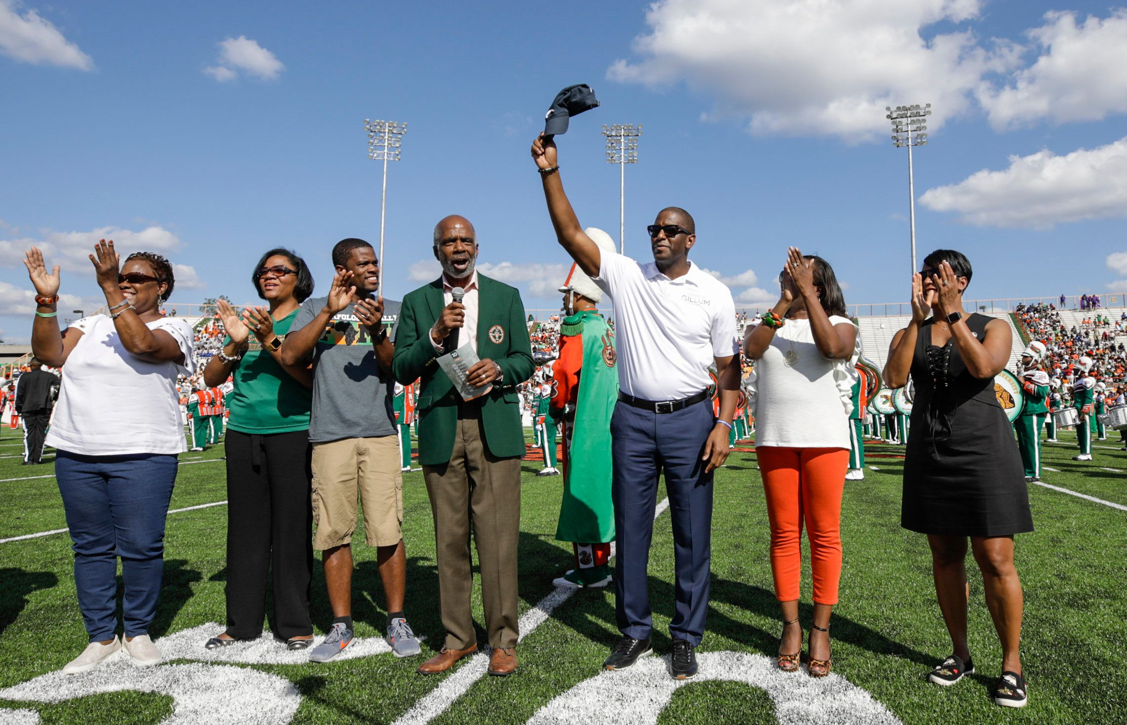 The Gillums stand with other FAMU alumni during the homecoming football game coin toss.