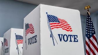 Looking up at empty portable voting booths with an American flag decal and the word 'VOTE' on the sides and an American Flag with a Bald eagle on top in the background of a polling station.