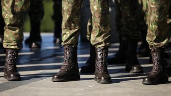 Details with the uniforms, gloves, boots and handguns of soldiers staying in line