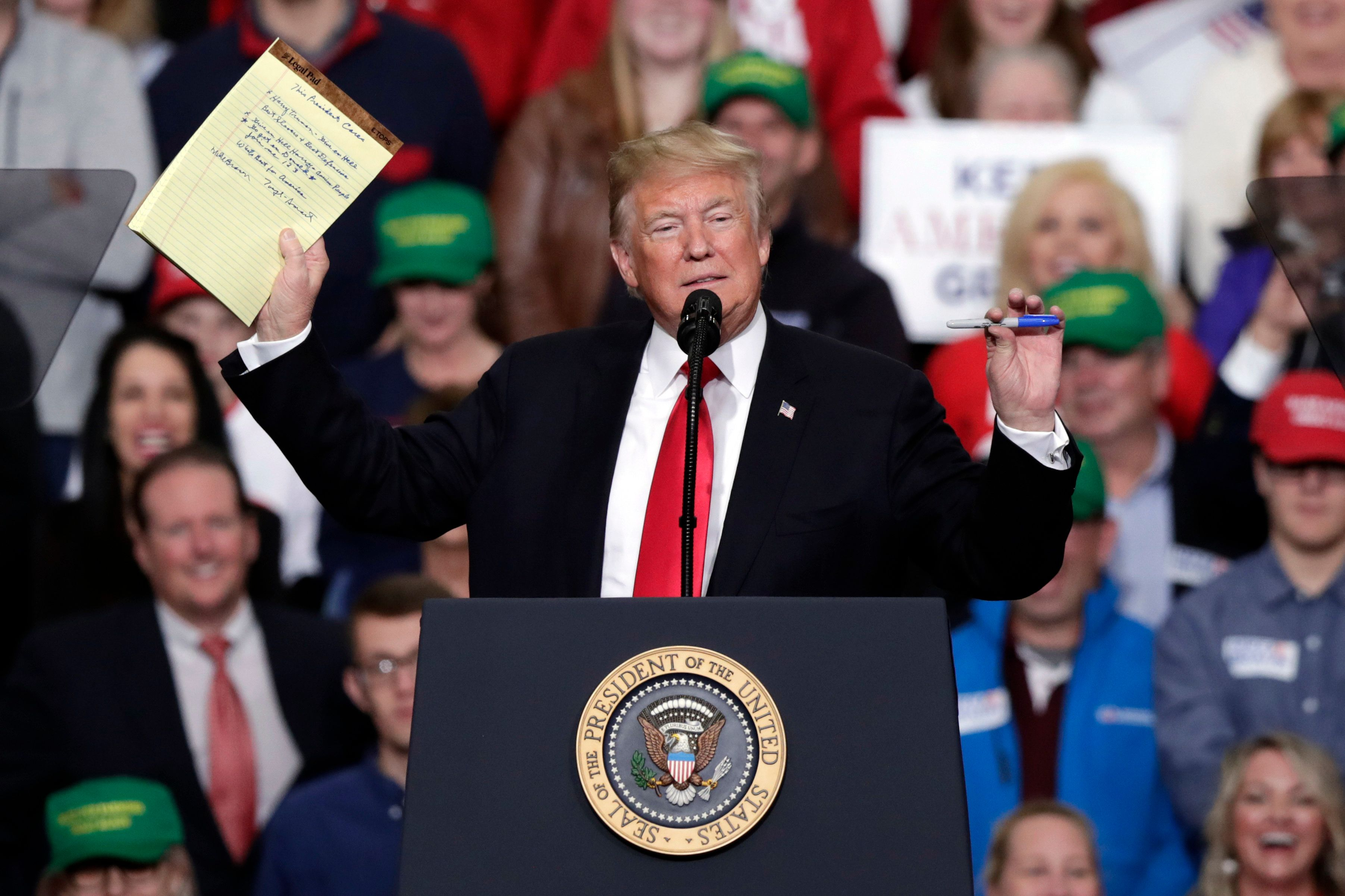 President Donald Trump shows the notes left behind by former basketball coach Bob Knight speaks at a campaign rally in Indianapolis, Friday, Nov. 2, 2018. (AP Photo/Michael Conroy)