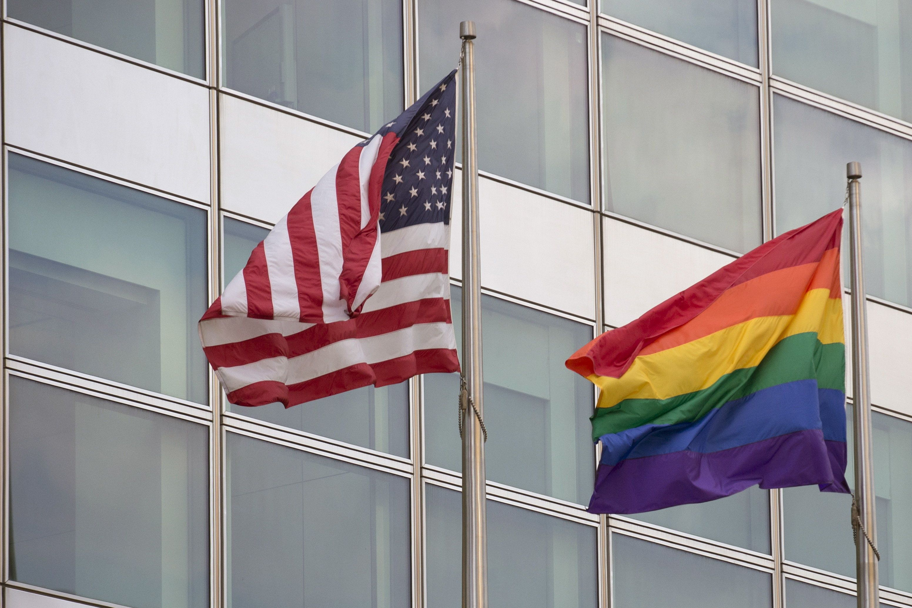 A gay pride flag flies along side the U.S. flag (L) in front of 200 West Street, also known as the Goldman Sachs Tower, in lower Manhattan in New York June 26, 2015. The Supreme Court ruled on Friday that the U.S. Constitution provides same-sex couples the right to marry, handing a historic triumph to the American gay rights movement. REUTERS/Brendan McDermid