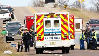 Multiple ambulances stage Saturday, Nov. 3, 2018 in response to a hit-and-run accident that killed two area Girl Scouts and one adult on County Highway P in the Village of Lake Hallie, Wis. It is believed the victims were picking up roadside litter when struck by a black or gray Ford F-150 pickup that left the scene. Two other children suffered serious injuries in the crash. (AP Photo, Eau Claire Leader-Telegram, Steve Kinderman).