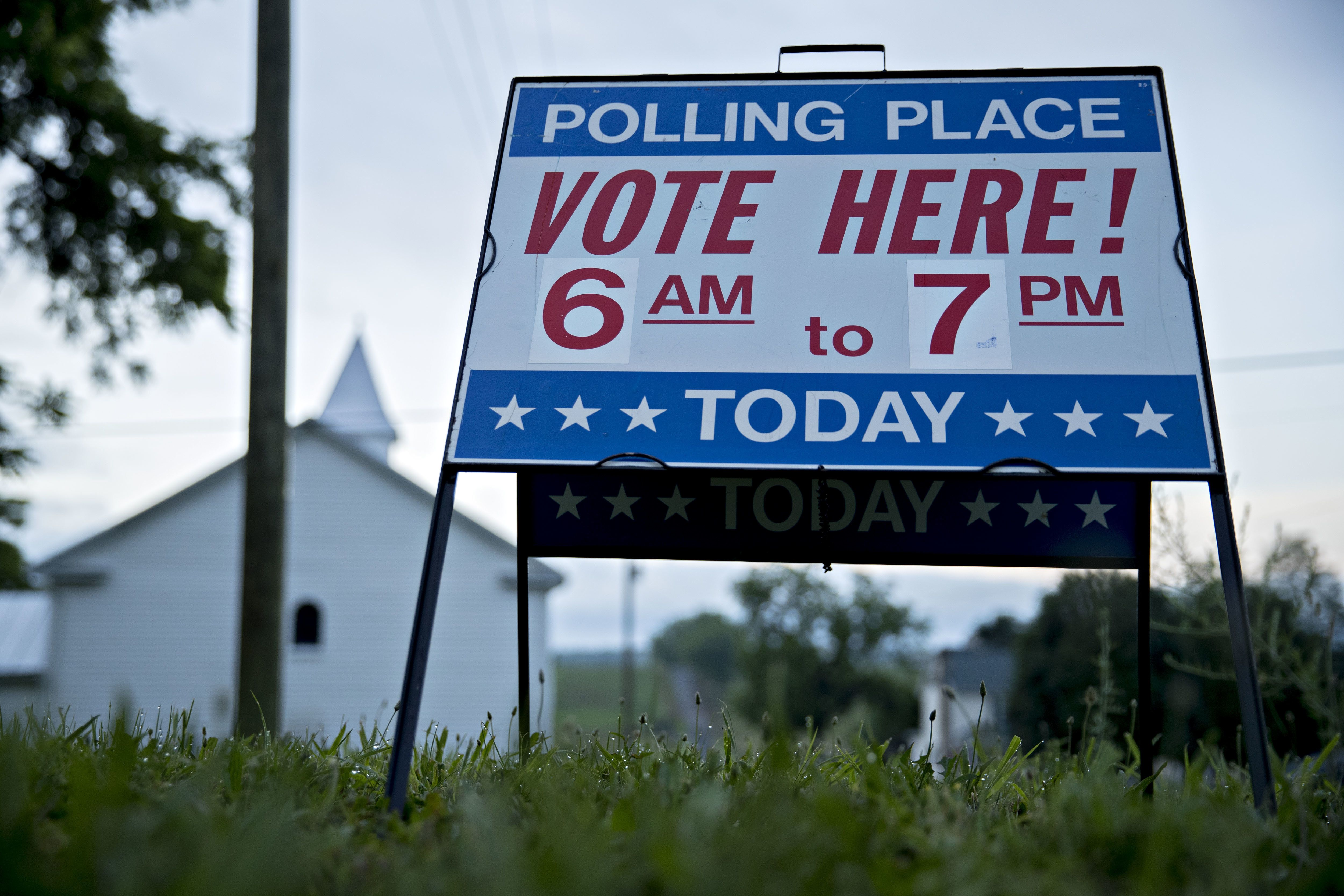 A 'Vote Here!' sign stands outside a polling location during the primary election in Lebanon Church, Virginia, U.S., on Tuesday, June 12, 2018. In the Shenandoah Valley's 6th Congressional district, four Democrats are running in the primary for the open seat being vacated by retiring Republican Bob Goodlatte. Photographer: Andrew Harrer/Bloomberg via Getty Images