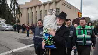 FILE - In this Oct. 29, 2018, file photo, Rabbi Jeffrey Myers, center, of Tree of Life synagogue, carries their Torah to be stored elsewhere in Pittsburgh. A team of rabbis and volunteers had gone into the Tree of Life synagogue to gather up blood and other remains from the victims of the shooting rampage, in keeping with Jewish law that says the entire body must be buried. (Charles Fox/The Philadelphia Inquirer via AP, File)
