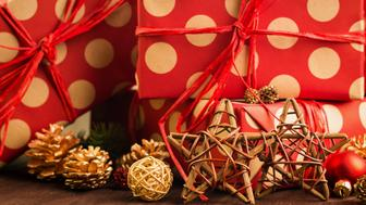 Christmas and New Year's Day festive decoration, red and golden balls, multicolored fir cones and branches, wooden stars with presents wrapped in red paper with golden circles on brown wood background. Copy space for text.