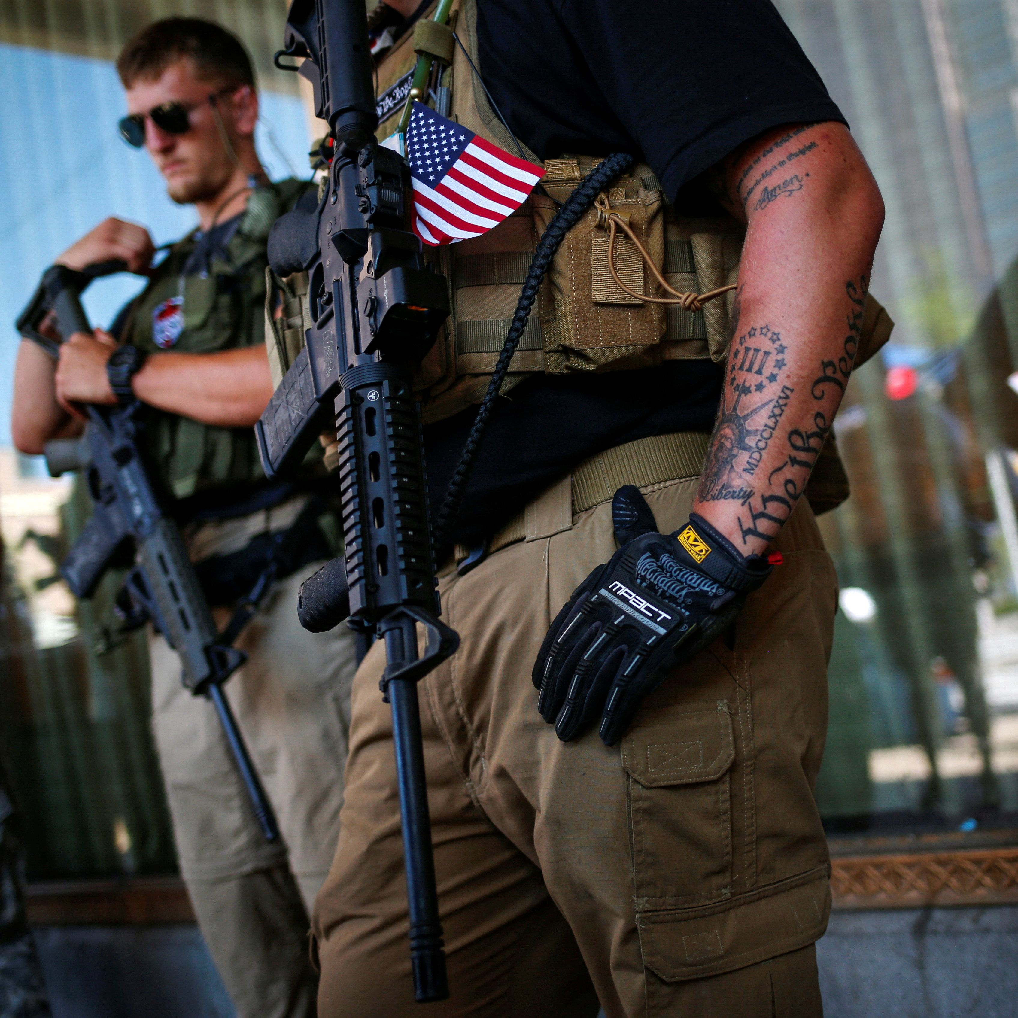 Members of the West Ohio Minutemen carry their assault weapons while taking a break from patrolling downtown Cleveland during the Republican National Convention in Ohio, U.S., July 19, 2016. REUTERS/Adrees Latif