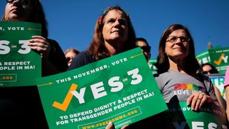 BOSTON, MA - SEPTEMBER 16: Camille Ernst, center, and Joanne Hooker, right, hold signs for a 'Yes on 3' rally in Boston's Copley Square on Sep. 16, 2018. Question 3 on the state ballot in November concerns discrimination against transgender people in places of public accommodation. A 'yes' vote would keep in place a current law prohibiting discrimination on the basis of gender identity. (Photo by Michael Swensen for The Boston Globe via Getty Images)