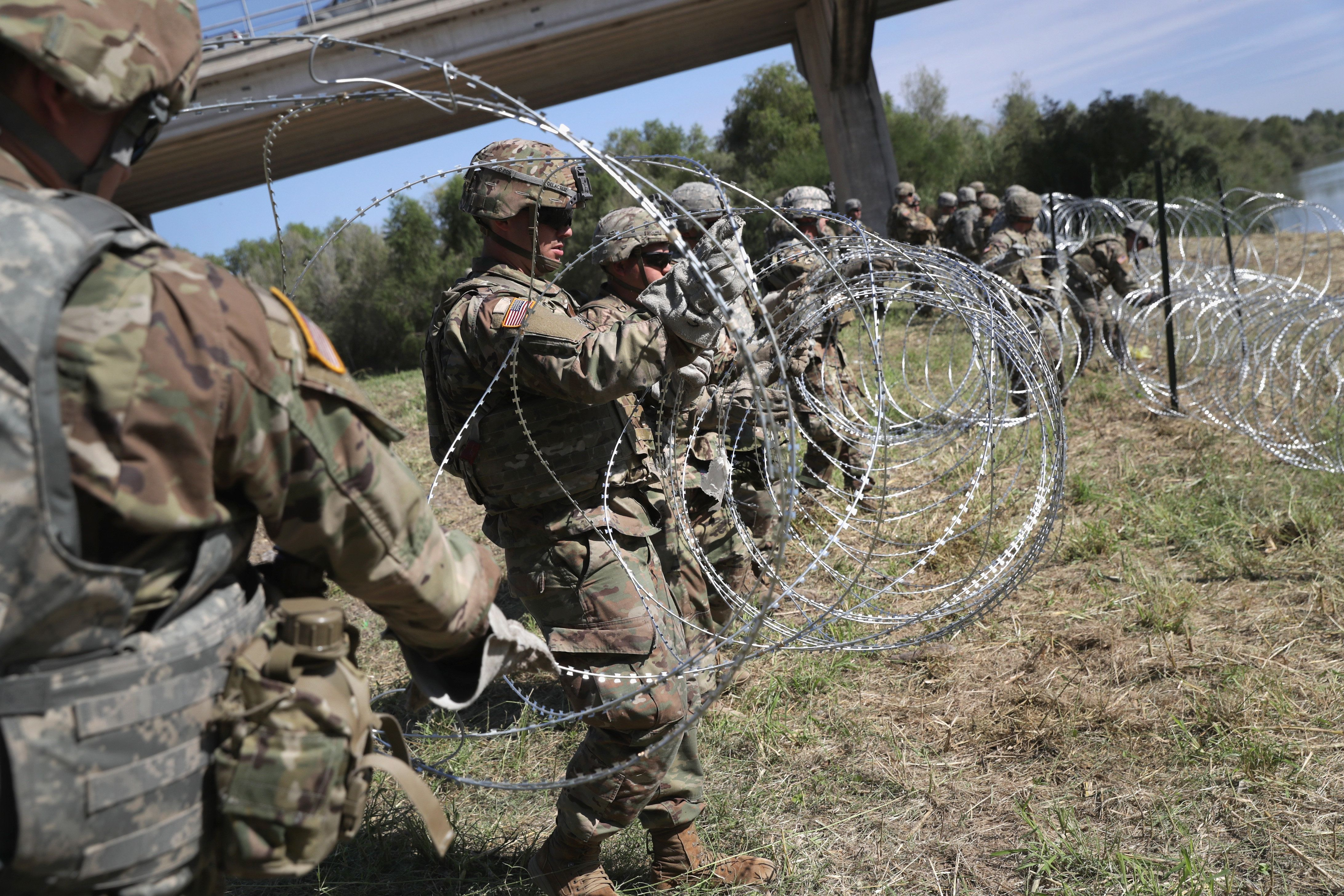 HIDALGO, TX - NOVEMBER 02:  U.S. Army soldiers from Ft. Riley, Kansas install protective wire along the Rio Grande at the U.S.-Mexico border on November 2, 2018 in Hidalgo, Texas. U.S. President Donald Trump ordered the troops to the border to bolster security at points of entry where an immigrant caravan may attempt to cross in upcoming weeks. The troops in Hidalgo were from the 97th MP Battalion and had arrived to the Rio Grande Valley the day before.  (Photo by John Moore/Getty Images)