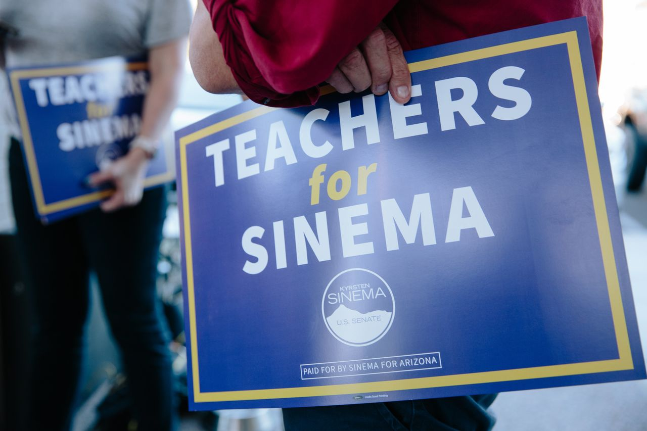 Supporters of #RedForEd hold signs touting Sinema on Oct. 24 in Phoenix.