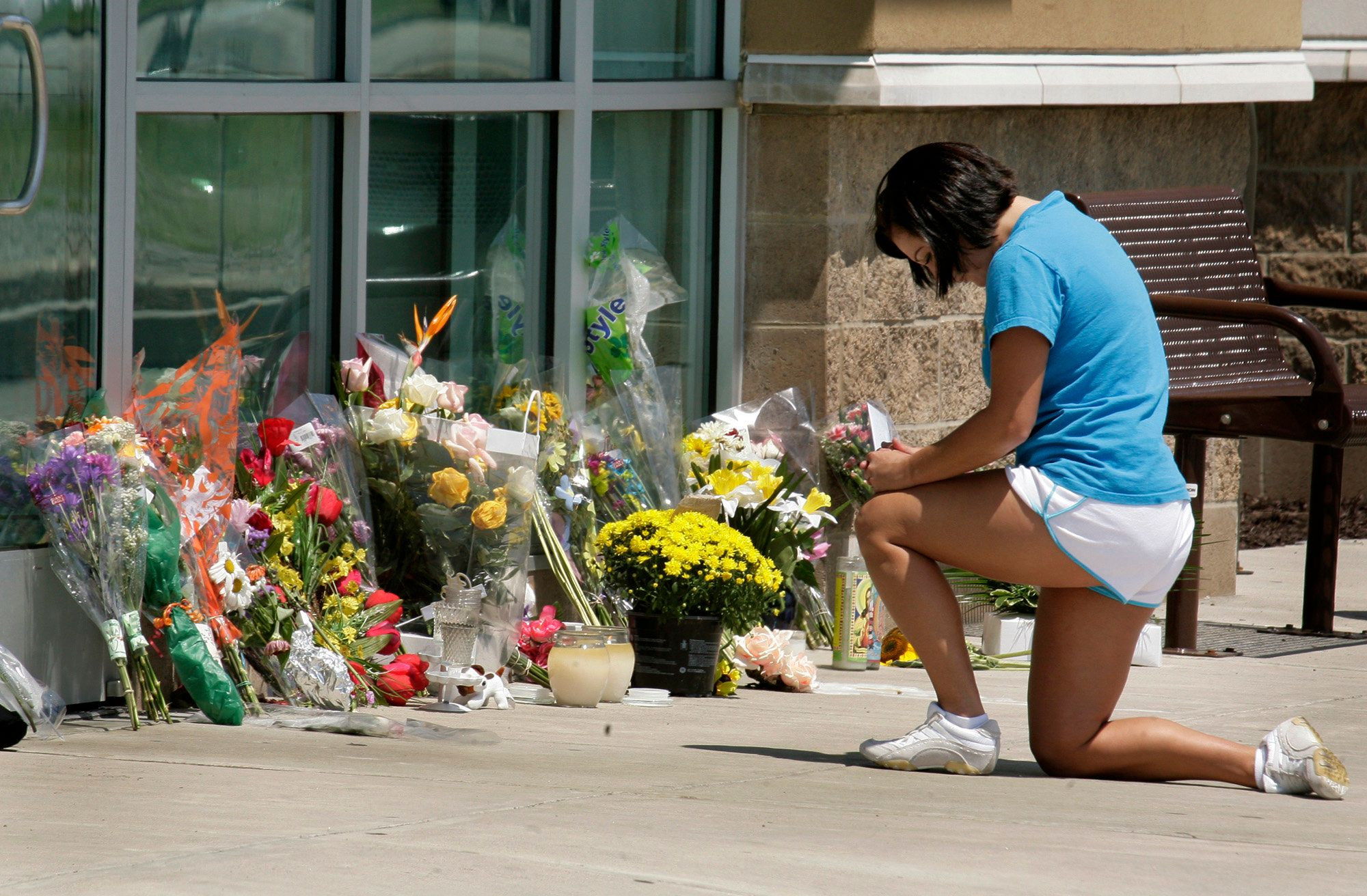 A woman places flowers outside an LA Fitness in Collier Township, Pennsylvania, on Aug. 6, 2009, after George Sodini&nbs