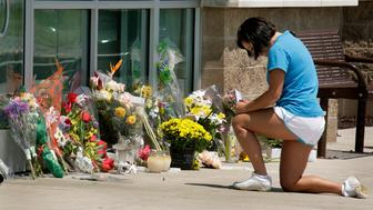 Lauren Jakubovich of Greentree, Pa., takes a moment to pray after placing flowers outside the LA Fitness club, where she is a member, Thursday, Aug. 6, 2009 in Bridgeville, Pa.. Police say a gunman opened fire after walking into an exercise class at the club Tuesday night, killing three women before taking his own life.  (AP Photo/Gene J. Puskar)