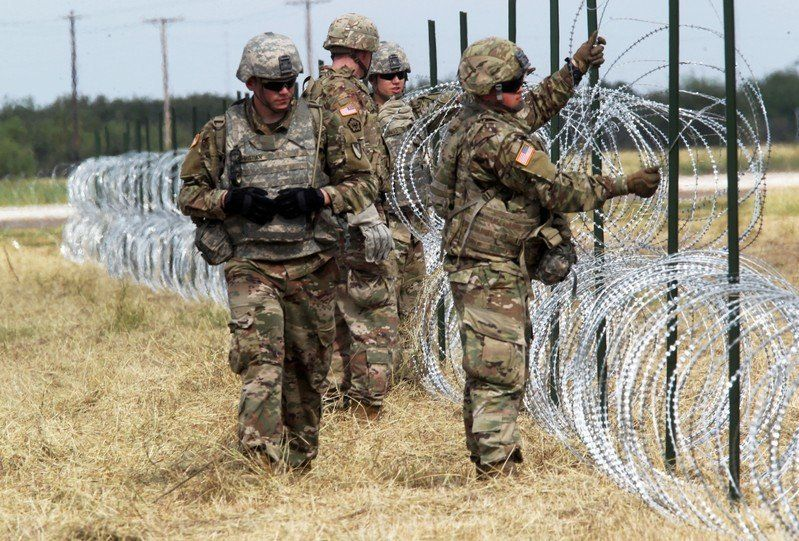 U.S. Army soldiers put up barbed wire fence for an encampment to be used by the military near the U.S. Mexico border in Donna Texas