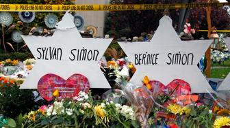 These are markers, outside the Tree of Life Synagogue on Saturday, Nov. 3, 2018, that are in remembrance of married couple Sylvan and Bernice Simon, who killed by a gunman, along with 9 others, while they worshiped Oct 27, 2018 at the Tree of Life Synagogue in the Squirrel Hill neighborhood of Pittsburgh. (AP Photo/Gene J. Puskar)