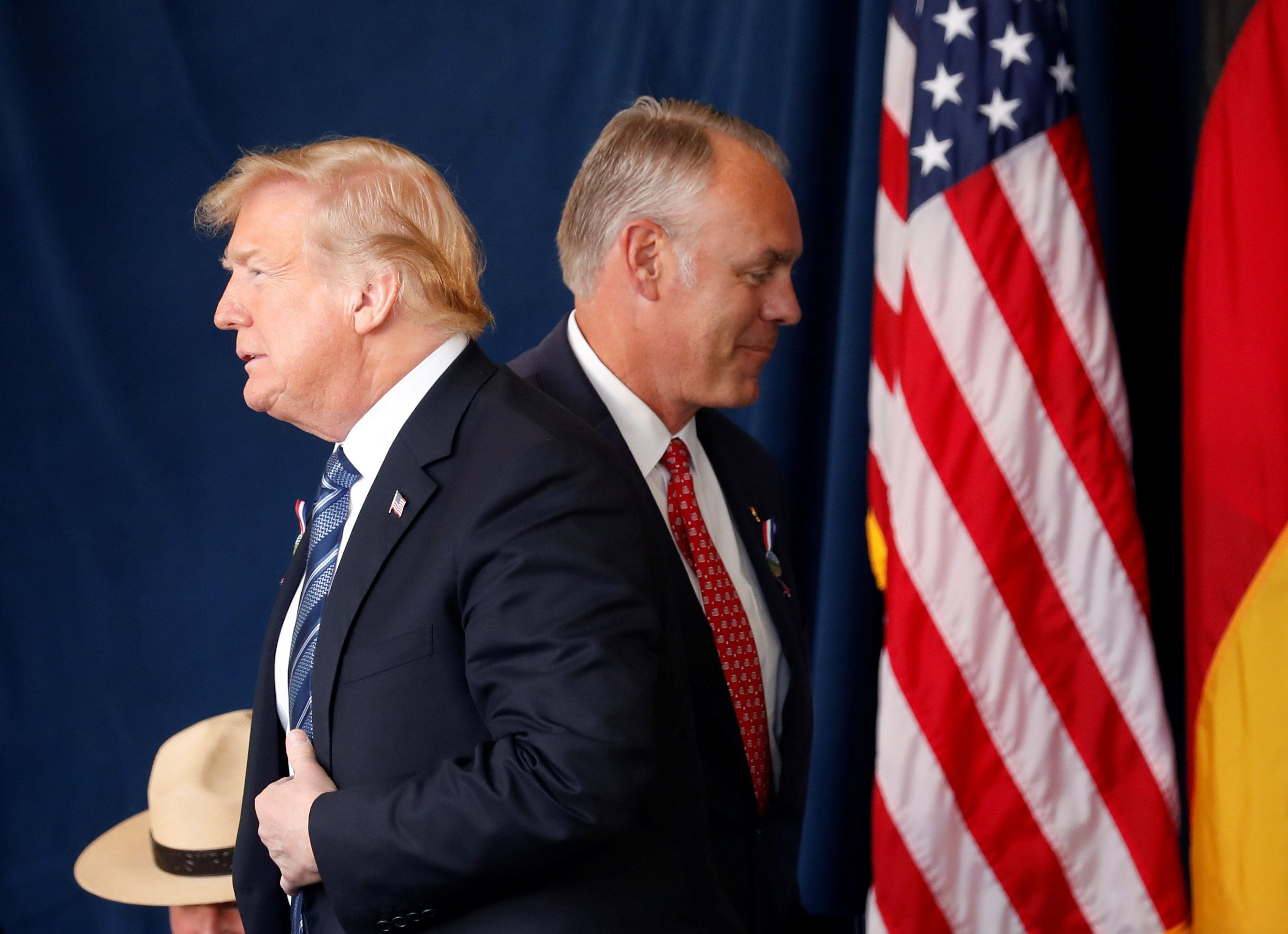 U.S. President Donald Trump walks past Interior Secretary Ryan Zinke as he stands to address the 17th annual September 11 observance at the Flight 93 National Memorial near Shanksville, Pennsylvania. REUTERS/Kevin Lamarque