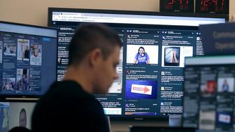 A man works at his desk in front of monitors during a demonstration in the war room, where Facebook monitors election related content on the platform, in Menlo Park, Calif., Wednesday, Oct. 17, 2018. (AP Photo/Jeff Chiu)