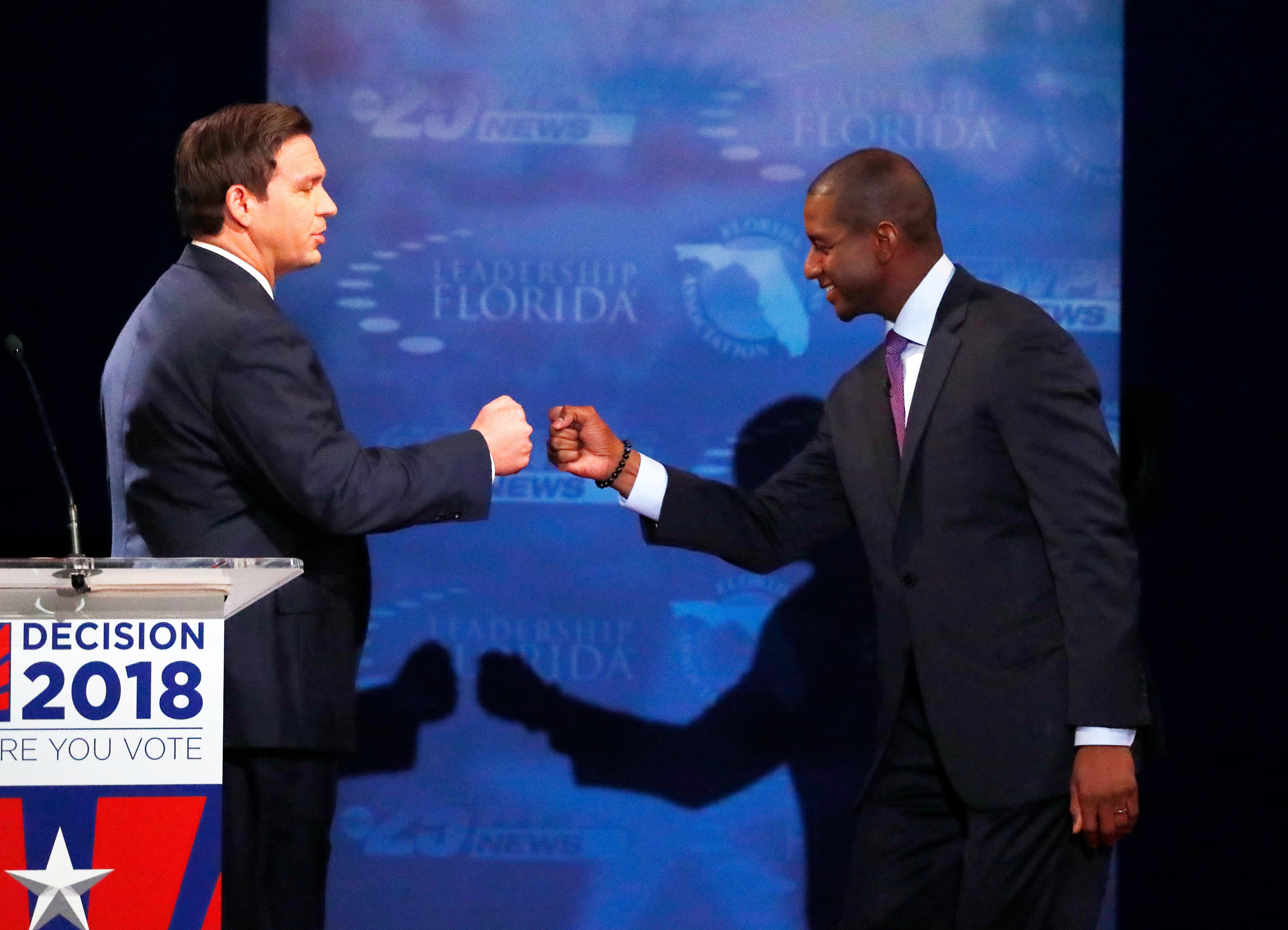 Republican Ron De Santis and Democrat Andrew Gillum fist-bump at their debate last month