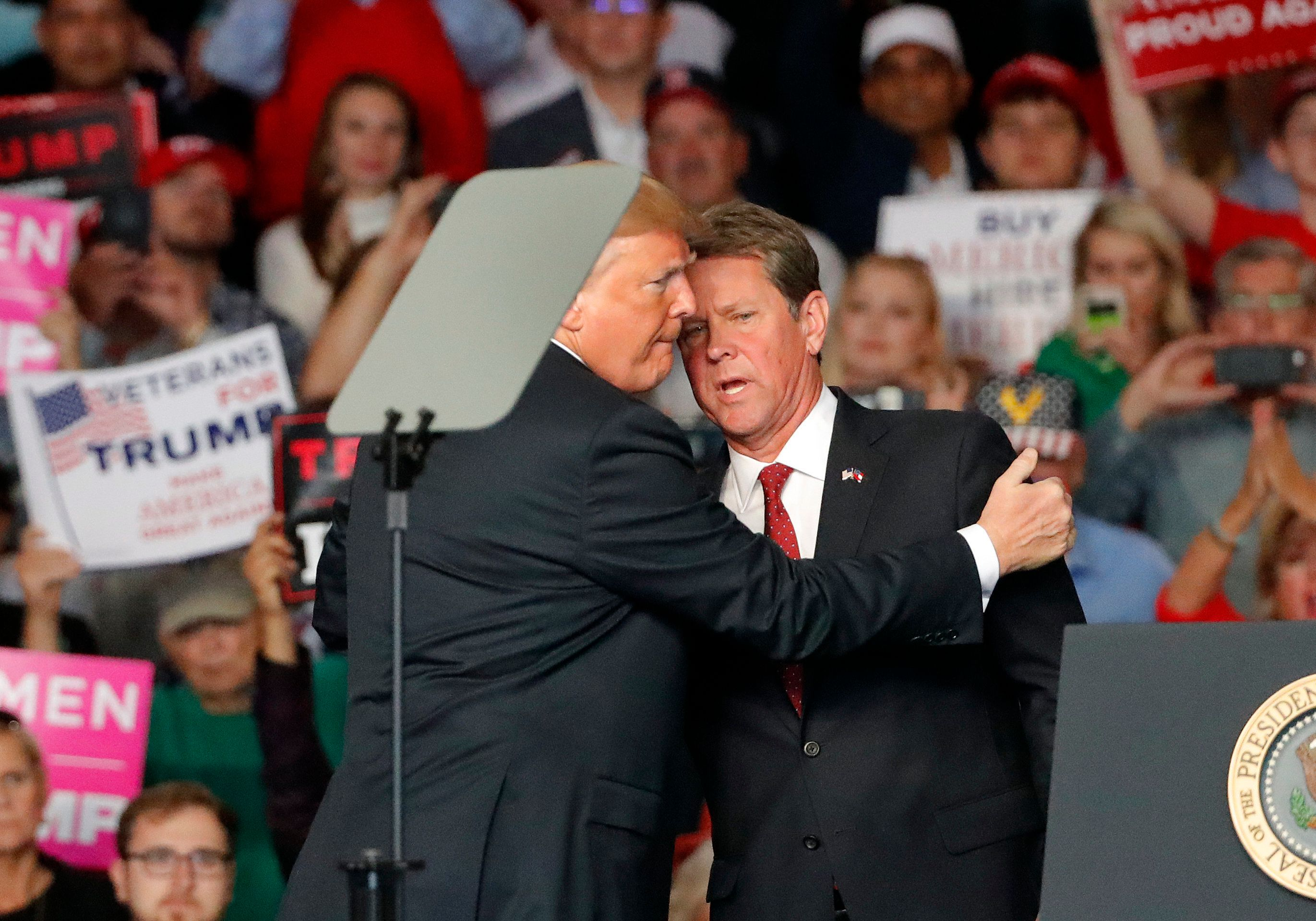 Georgia Republican gubernatorial nominee Brian Kemp, right, introduces President Donald Trump during a campaign rally Sunday, Nov. 4, 2018, in Macon, Ga. (AP Photo/John Bazemore)