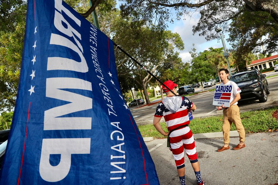 Mike Caruso campaign employee Isaac Rheinbolt, chats with a Trump supporter (who did not want to be identified) in the parking lot of the Boca Raton Community Center.&nbsp&#x3B;