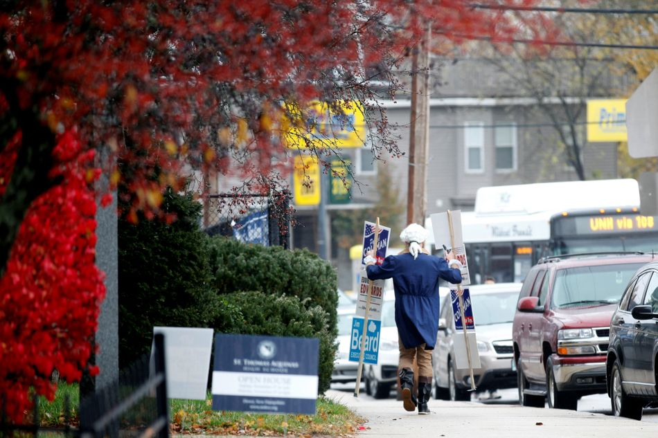 Patrick Coleman, a candidate for state representative, walks down the street with signs for himself, U.S. House of Representatives candidate Eddie Edwards, and others, in Dover, New Hampshire.&nbsp&#x3B;